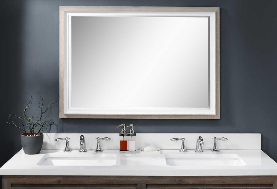A bathroom vanity is shown with a rectangle mirror and dark blue walls.